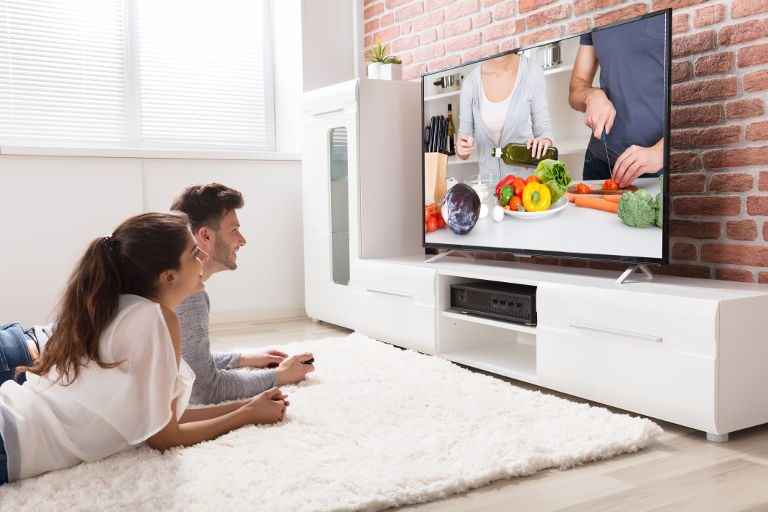 couple laying on rug in front of tv